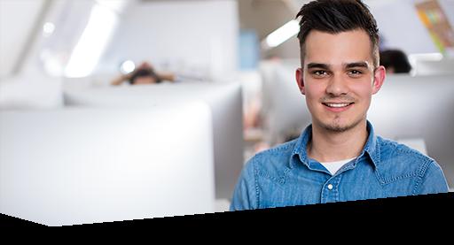Ein junger Mann im Mac-Raum der Dr. Buhmann Akademie in Hannover lächelt in die Kamera
