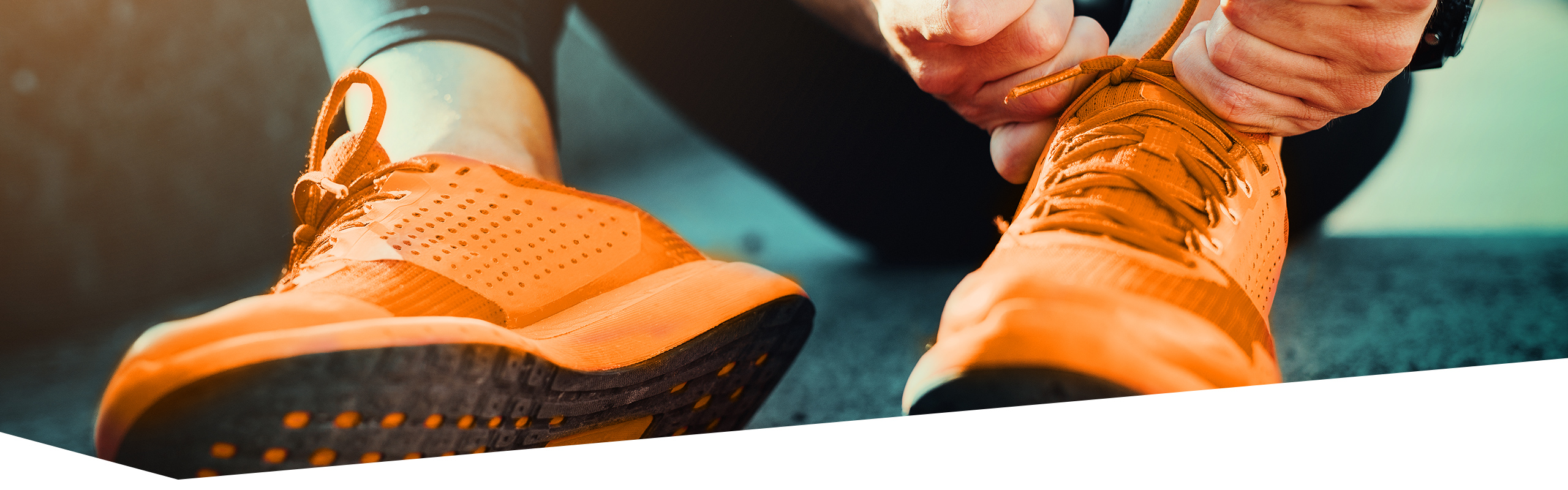Sportler schnürt sich orange Turnschuhe zu, dabei sind nur die Füße und Hände zu sehen