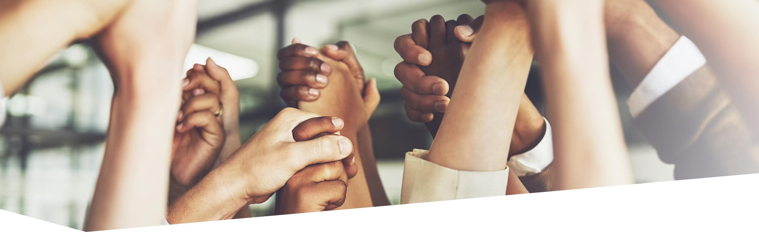 Hochgehaltene Hände mehrere Personen, die sich gegenseitig festhalten
