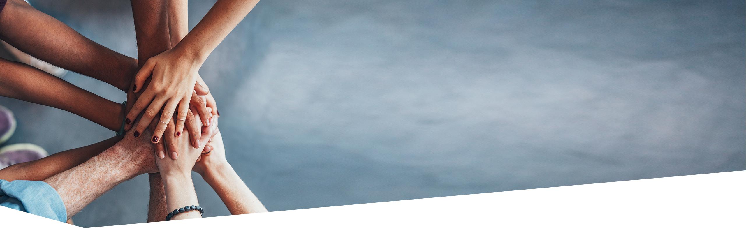 Links im Bild Hände von fünf Personen übereinander gelegt, Arme bilden Kreis, rechts graue Fläche