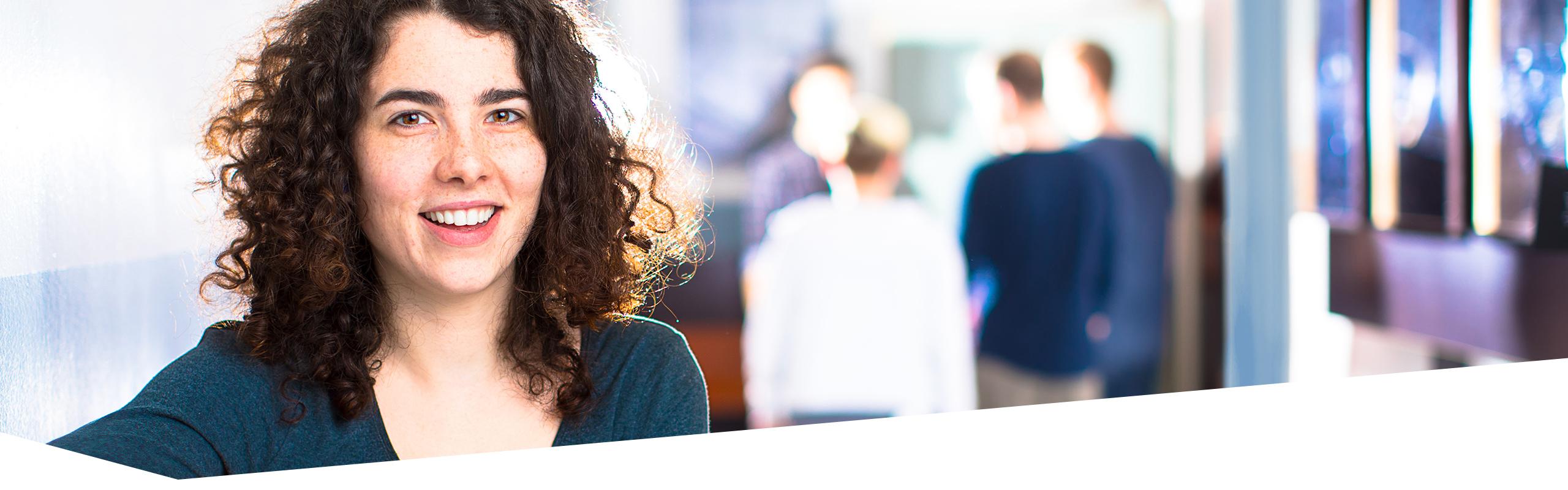 Gesicht einer Berufstätigen, die in die Kamera lächelt, vier Schüler im Hintergrund sprechen miteinander