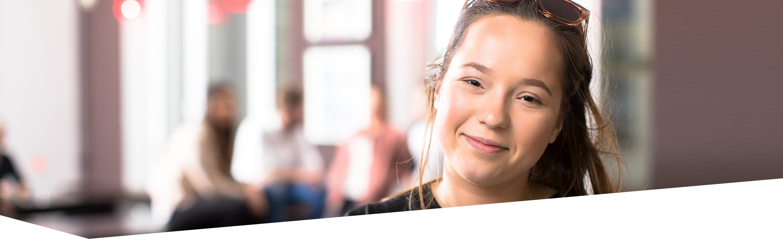 Junge Frau in der Ausbildung, die Betrachter anlächelt, weitere junge Menschen in der Ausbildung sprechen im Hintergrund miteinander