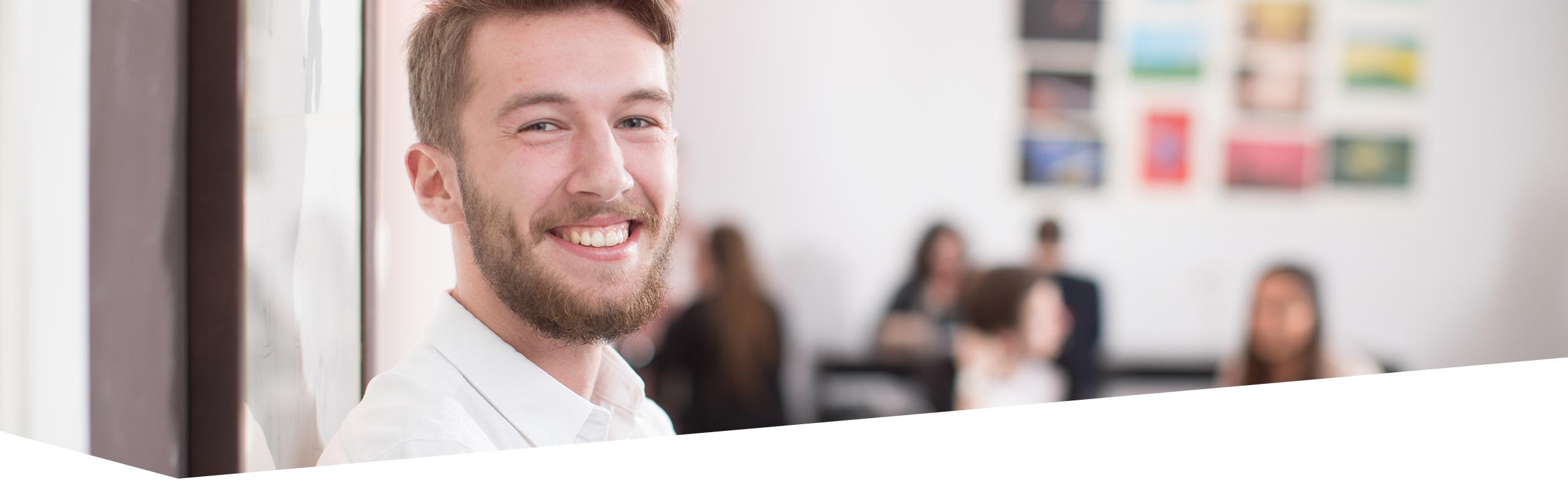Gesicht von Student, der den Betrachter anlächelt, Seminarraum mit weiteren Schülern im Hintergrund