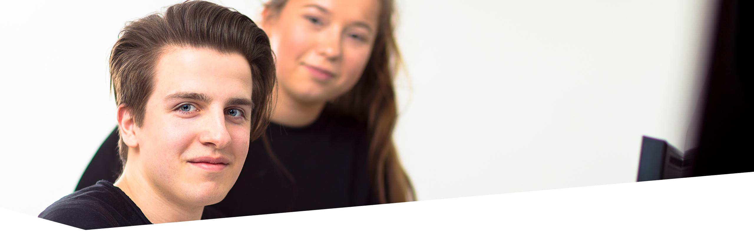 Schüler und Schülerin der Dr. Buhmann Schule und Akademie, die den Betrachter anlächeln