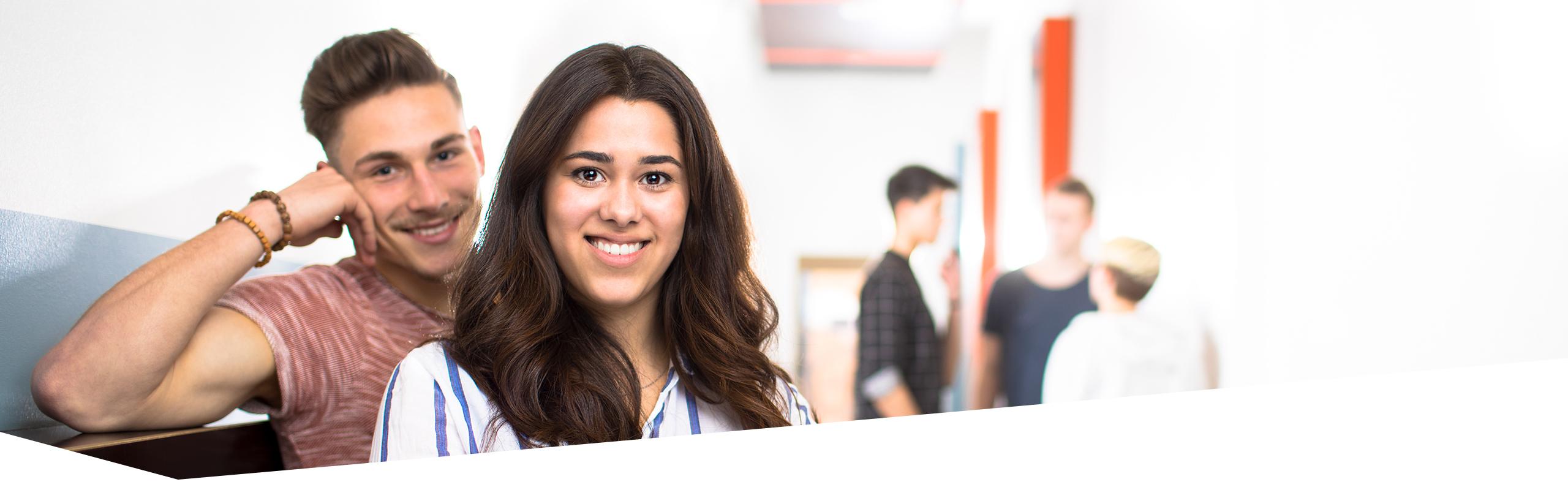 Gesicht von Schüler und Schülerin, die in die Kamera lächeln, drei Schüler im Hintergrund sprechen miteinander