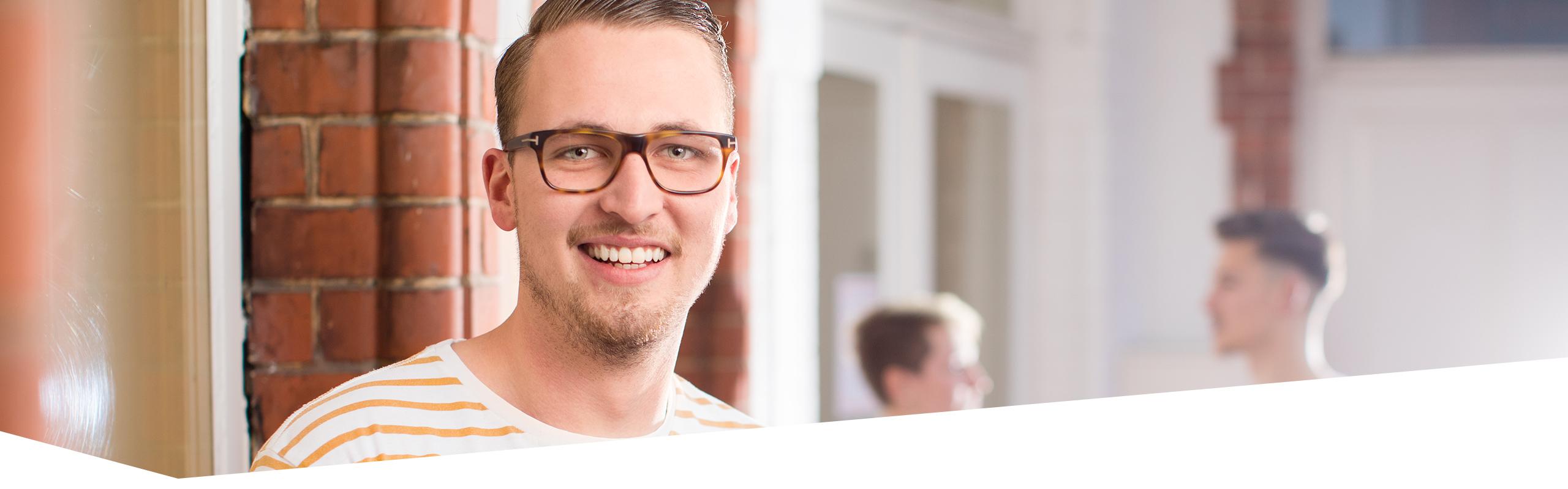 Gesicht von Berufstätigem, der Betrachter anlächelt, zwei Berufstätige sprechen im Hintergrund miteinander