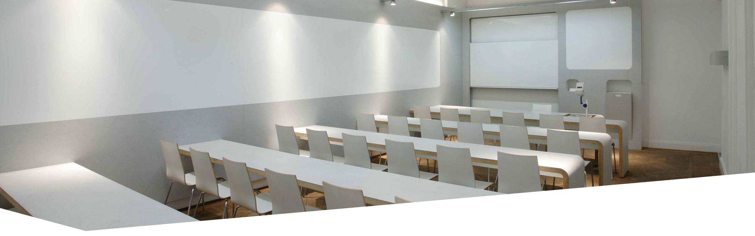 Leerer Seminarraum mit Tafel, Tageslichtprojektor und Tischreihen